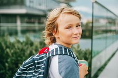 Outdoor portrait of funny little schoolboy. Close up portrait of young cute little 6 year old boy wearing backpack, back to school. Candid small schoollboy, film Royalty Free Stock Image