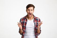 Close-up portrait of young emotional screaming man standing with Stock Photos