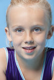 Close-up portrait of a young female gymnast over blue background Royalty Free Stock Image