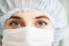 Close-up portrait of young female surgeon doctor or intern wearing protective mask and hat Royalty Free Stock Photo