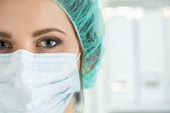 Close-up portrait of young female surgeon doctor. Or intern wearing protective mask and hat. Healthcare, medical education, emergency medical service, surgery Royalty Free Stock Image