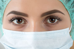 Close up portrait of young female surgeon doctor. Or intern wearing protective mask and hat. Healthcare, medical education, emergency medical service, surgery Stock Photo