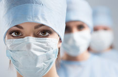 Close-up portrait of young female surgeon doctor. Surrounded by her team. Group of surgeon in operation theatre. Healthcare, medical education, emergency Royalty Free Stock Photos