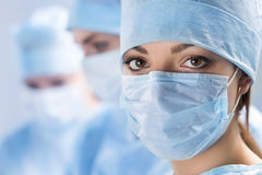 Close-up portrait of young female surgeon doctor. Close up portrait of young female surgeon doctor surrounded by her team. Group of surgeon in operation theatre Stock Photo