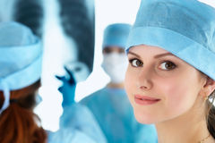 Close up portrait of young female surgeon doctor. Surrounded by her team. Group of surgeon in operation theatre. Healthcare, medical education, emergency Royalty Free Stock Photography