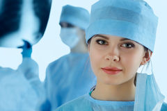 Close up portrait of young female surgeon doctor. Surrounded by her team. Group of surgeon in operation theatre. Healthcare, medical education, emergency Stock Photography