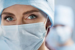 Close-up portrait of young female surgeon doctor. Close up portrait of female surgeon doctor wearing protective mask and cap. Healthcare, medical education Stock Photos