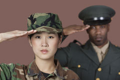 Close-up portrait of young female soldier with mal. E soldier saluting over brown background over brown background stock images