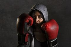 Close up portrait of young fit and healthy Asian Chinese boxer woman in fitness top hoodie and boxing gloves posing cool badass at royalty free stock photography