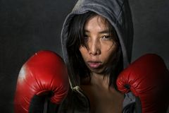 Close up portrait of young fit and healthy Asian Korean boxer woman in fitness top hoodie and boxing gloves posing cool badass att. Itude angry and defiant in stock photo