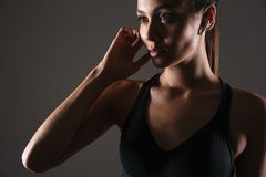 Close up portrait of a young fitness woman. Listening to music in earphones  over gray background Royalty Free Stock Images