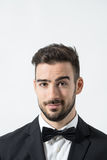 Close up portrait of young friendly charming gentleman with raised eyebrow looking at camera. Portrait over gray studio background Royalty Free Stock Photo