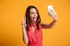 Close-up portrait of young funny brunette woman makes selfie on Royalty Free Stock Photography