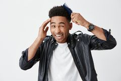 Close up  portrait of young funny dark-skinned attractive men with curly hair in fashionable outfit combing hair Stock Photos