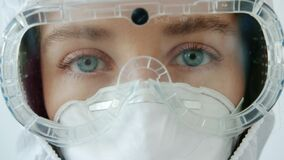Close-up portrait of young girl doctor in safety suit goggles and respirator on white background
