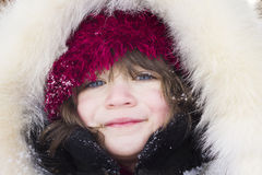 Close-up portrait of young girl wearing fur hood and smiling Royalty Free Stock Photo