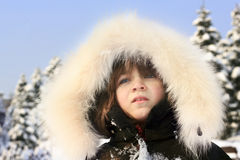 Close-up portrait of young girl wearing fur hood and smiling Stock Image