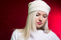 Close-up portrait of a young girl in a white cap and sweater Stock Photo