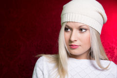 Close-up portrait of a young girl in a white cap and sweater on Stock Image