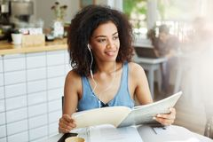 Close up portrait young good-looking black-skinned woman with curly hair in casual clothes sitting in cafeteria. Drinking coffee, listening music in earphones Stock Image