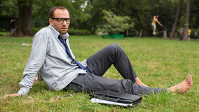 Close-up portrait of young good looking businessman. He is sitting on a grass. Stock Photos