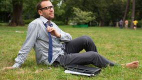 Close-up portrait of young good looking businessman. He is sitting on a grass. Stock Photography