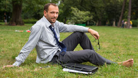 Close-up portrait of young good looking businessman. He is sitting on a grass. Royalty Free Stock Photos
