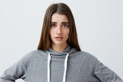 Close up portrait of young good-looking unhappy caucasian girl with dark long hair in casual grey hoodie crying, looking. In camera with wet eyes after breakup Stock Images
