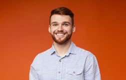 Close up portrait of young guy with beautiful smile. On orange background, panorama, copy space royalty free stock images