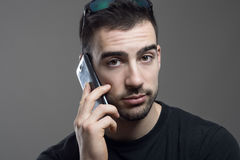 Close up portrait of young handsome bearded man in black shirt talking on the phone looking Stock Images