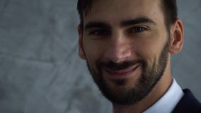 Close up portrait of young handsome bussinesman in dark blue suit look in camera and smile slow motion. stock video