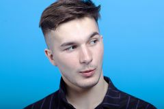 Close up portrait of young handsome man with astonished grimace on blue background.  Fashion hairstyle, strong emotions, expressiv royalty free stock image
