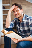 Close up portrait of a young handsome man reading book Royalty Free Stock Photography
