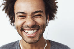 Close up portrait of young happy african man smiling listening to upbeat streaming music laughing over white background Stock Photos