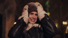 Close up portrait of young happy attractive girl in winter hat and mittens walking in falling snow at evening street