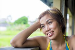Close up portrait of young happy beautiful Asian woman from Indonesia looking thoughtful and pensive daydreaming and thinking Royalty Free Stock Photo