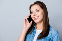 Close up portrait of young, happy, brunette girl having nice con. Versation on smart phone with friend, standing over grey background Stock Images
