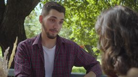Close-up portrait of young happy couple sitting outdoors at the table talking friendly and smiling to each other. Close-up portrait of the young happy couple stock footage