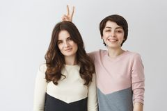 Close up portrait of young happy lesbian pair with dark hair in matching clothes smiling, having fun, posing for shoot. In photo booth Stock Image