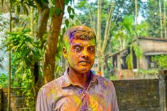 Close up portrait of young Indian man with Holi colors on face during Holi festival in India. royalty free stock image