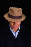 Close up portrait of young indigenous latin american man. Wearing a poncho and a hat over black background Royalty Free Stock Photo