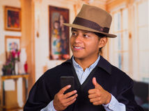 Close up portrait of young indigenous man wearing hat and poncho using cell phone Royalty Free Stock Photos