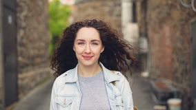 Close-up portrait of young lady happy tourist standing in the street against buildings in beautiful town and smiling. Close-up portrait of cheerful young lady stock footage