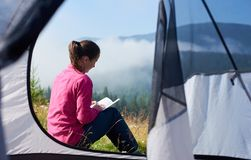 Young woman having a rest near tourist tent in the summer morning in the mountains stock image