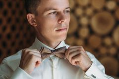Close-up portrait of young male businessman is getting dressed for work. A blond guy in a white shirt is trying on a bow Stock Photos