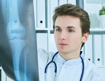 Close up portrait of young male doctor holding x-ray or roentgen image. Close up of male Caucasian doctor holding x-ray or roentgen image Stock Photos