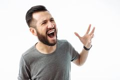 close-up portrait of a young man with a beard, wearing a gray t-shirt, with an irritated expression, shouting in anger, hands in royalty free stock photo