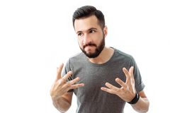 Close-up portrait of a young man with a beard, wearing a gray t-shirt , with an irritated expression, hands in the air, isolated w stock photos