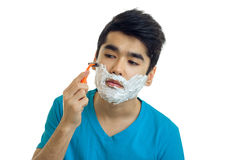 A close-up portrait of young man with foam beard which seriously shaves machine Royalty Free Stock Photos