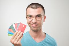 Close up portrait of young man in glasses holding a lot of gredit cards. Concept of non cash finance or being rich stock photos